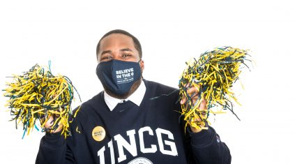 African American male student wearing blue and gold with pompoms