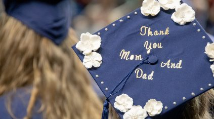 "A blue mortarboard on a graduate's head, with the words ""Thank you Mom and Dad"""